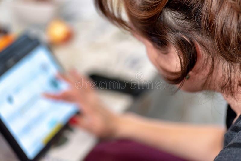 Изображение крупного плана руки ` s женщины держа черную таблетку и печатая на экране стоковые фото