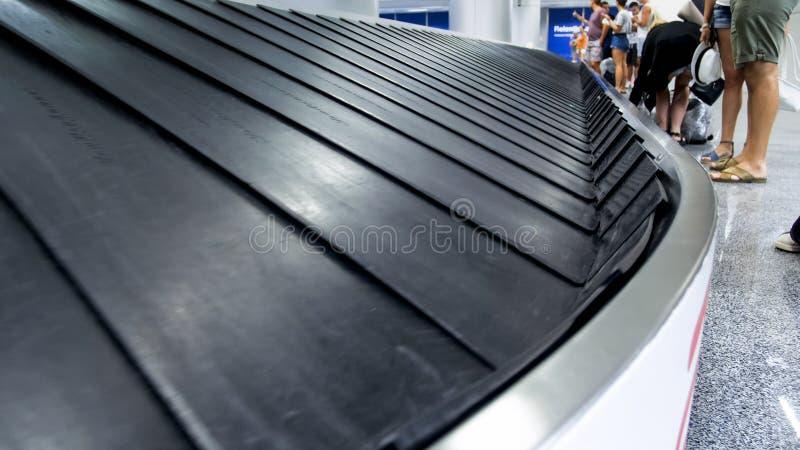 Изображение крупного плана туристов ждать багаж ther на линии заявки багажа в терминале стоковая фотография rf