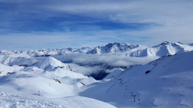 Изображение лыжного курорта в горах с низким стратусом над долинами стоковые изображения