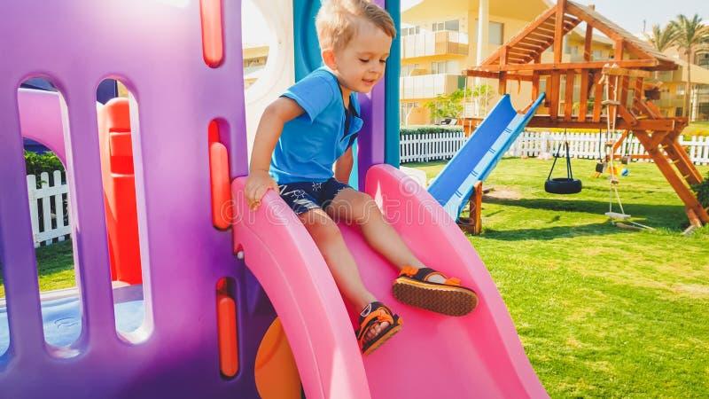 Изображение маленьких 3 старого лет мальчика малыша испуганного ехать на высоком скольжении на спортивной площадке стоковое изображение rf