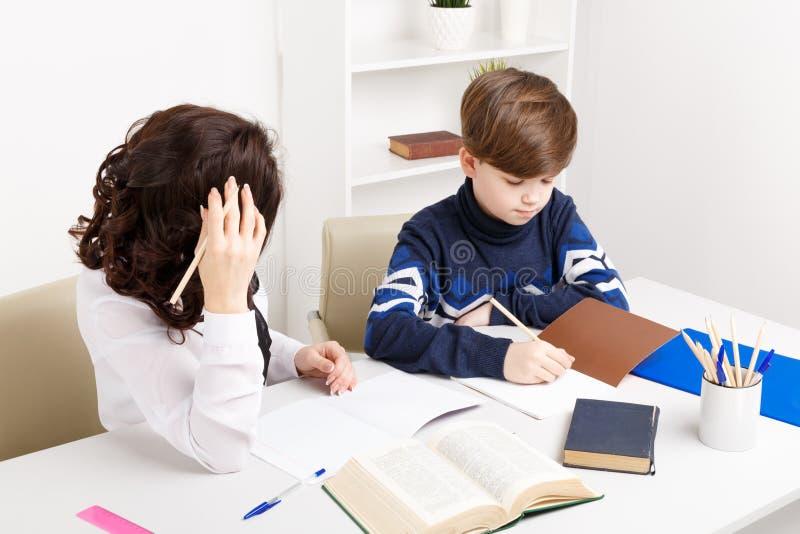 Изображение мальчика делая его домашнюю работу и его мать помогает ему стоковые изображения