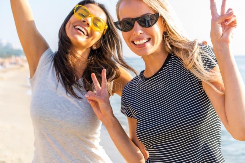 Изображение 2 многонациональных девушек 20s в стильной одежде смеясь над и наслаждаясь летним временем во время партии пляжа на в стоковое фото