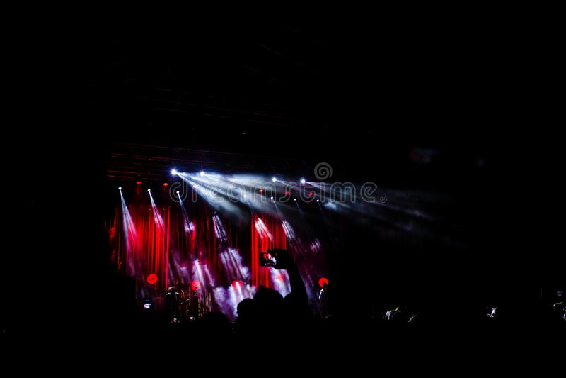 Изображение много людей наслаждаясь представлением ночи, большими непознаваемыми танцами толпы с поднятыми вверх руками и мобильн стоковые фотографии rf