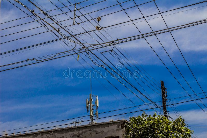 Изображение много электрических кабелей с парой ботинок вися от их стоковая фотография