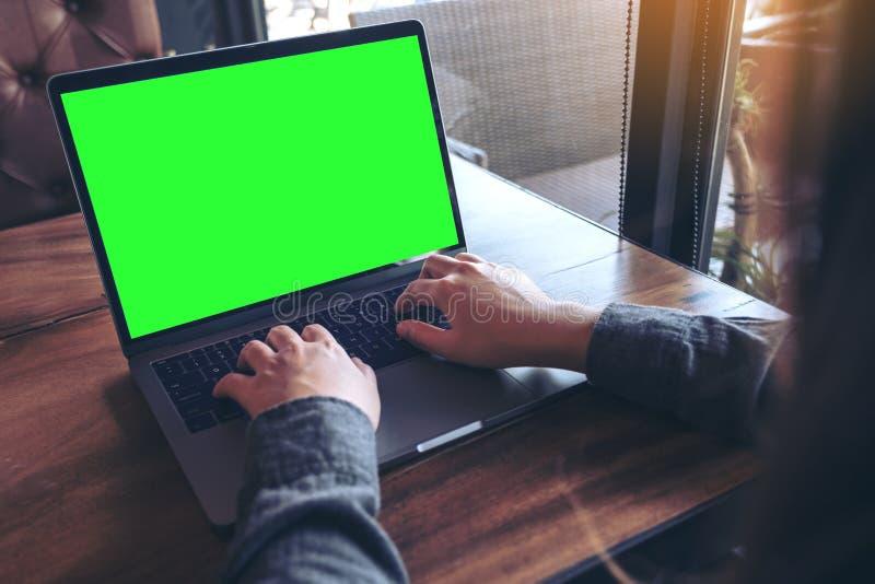 Изображение модель-макета бизнес-леди используя и печатающ на компьтер-книжке с пустыми белыми экраном и кофейной чашкой на табли стоковое фото rf