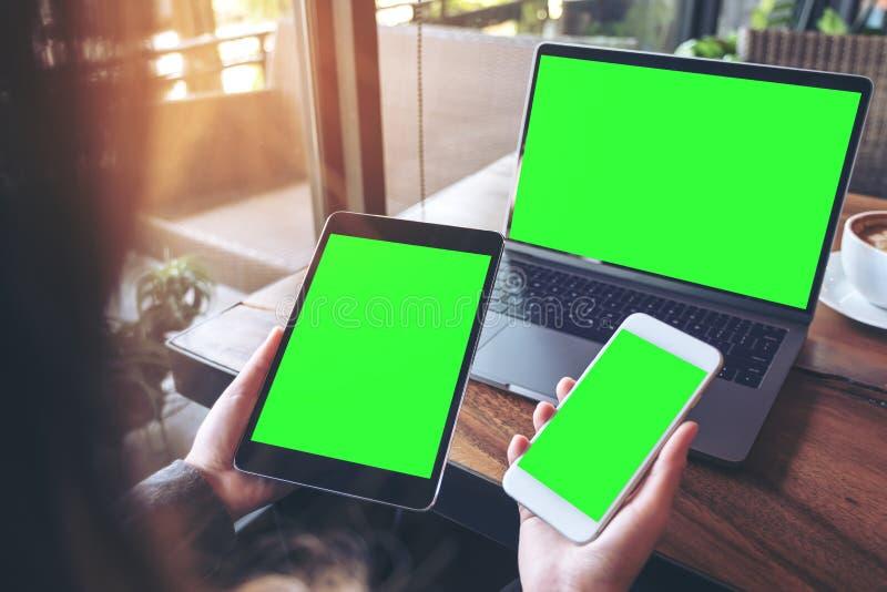 Изображение модель-макета коммерсантки держа белый мобильный телефон, черную таблетку и компьтер-книжку с пустым зеленым экраном  стоковое фото rf
