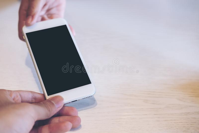 Изображение модель-макета удерживания руки, показывая и давая белый умный телефон с пустым черным экраном к другой персоне для то стоковые фото