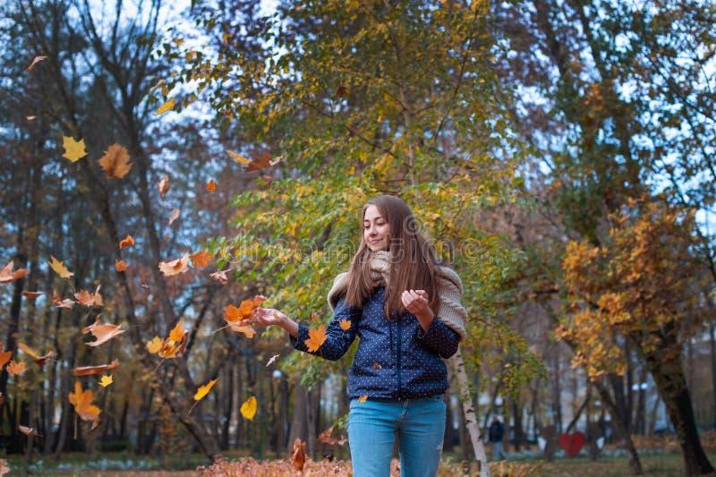 Изображение моды образа жизни Outdoors листьев счастливой красивой девушки бросая вверх в воздухе в парке осени стоковое изображение rf