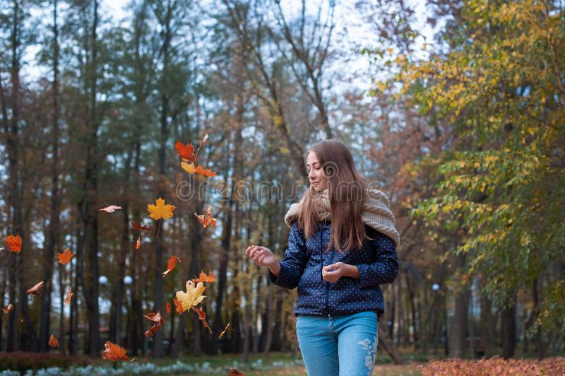 Изображение моды образа жизни Outdoors листьев счастливой красивой девушки бросая вверх в воздухе в парке осени стоковая фотография