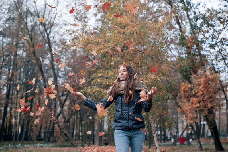 Изображение моды образа жизни Outdoors листьев счастливой красивой девушки бросая вверх в воздухе в парке осени стоковое фото