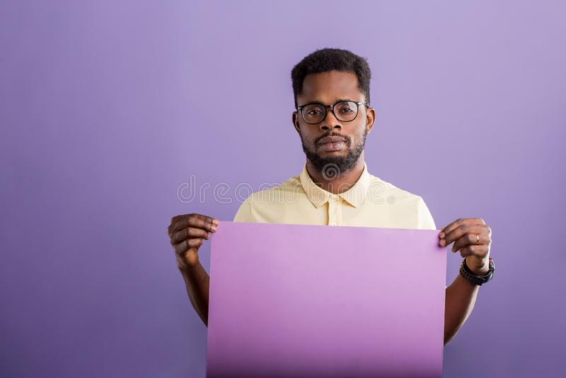 Изображение молодого Афро-американского человека держа пустую доску на фиолетовой предпосылке стоковые изображения
