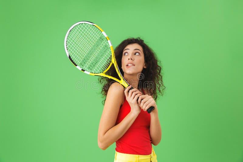 Изображение молодого женского теннисиста 20s усмехаясь и держа ракетку стоковые изображения rf