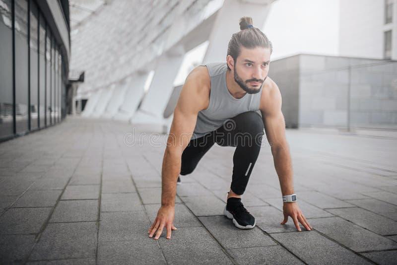 Изображение молодого человека готовое для бега Он стоит в положении спринта и выглядит прямодушным Гай готов побежать быстро он стоковые изображения