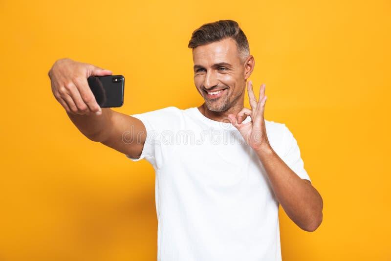 Изображение молодого человека 30s в белой футболке усмехаясь и принимая фото selfie на мобильном телефоне стоковые фотографии rf