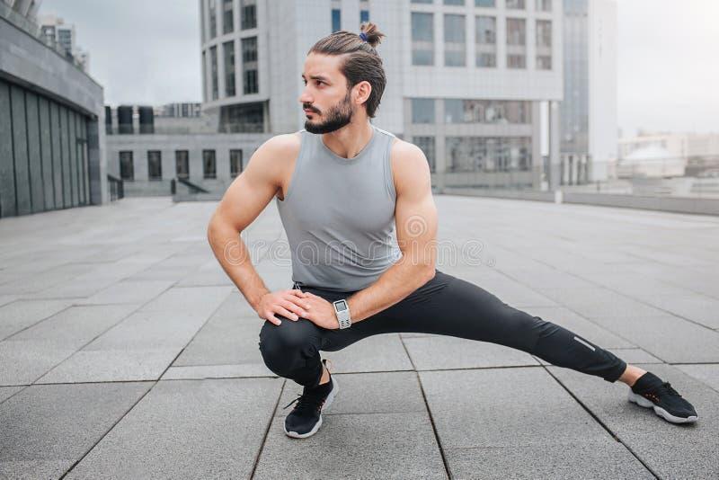 Изображение молодого человека stratching его нога и нагревая Он делает небольшие тренировки для ног Гай смотрит к выйденный Он де стоковое изображение rf