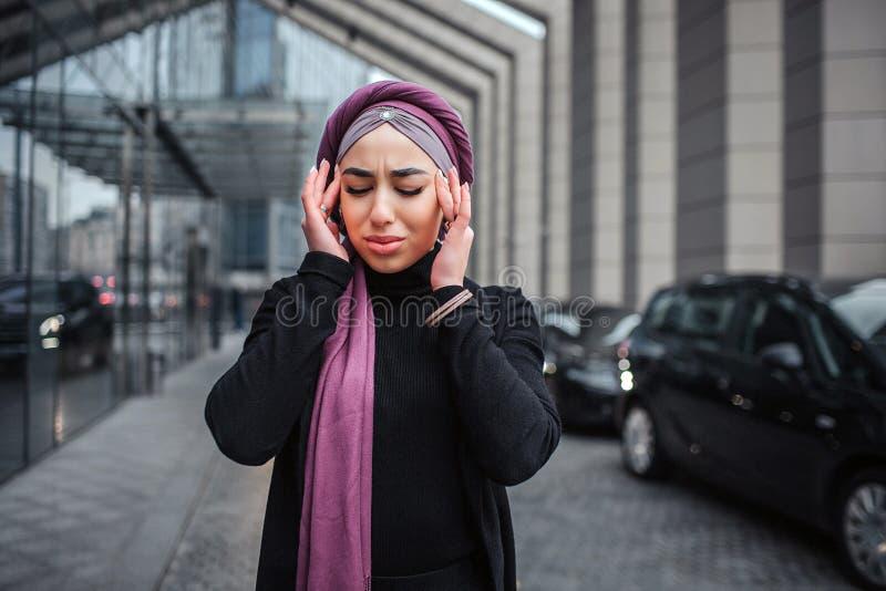 Изображение молодой аравийской стойки женщины снаружи Она держит руки близко к голове и держит глаза закрытый Модель имеет головн стоковое фото