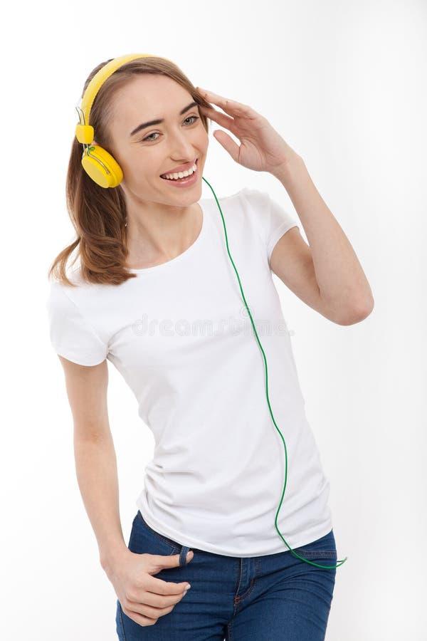 Изображение молодой девушки битника нося пустую белую футболку и голубые джинсы и слушают к музыке на белизне Насмешка вверх скоп стоковые изображения