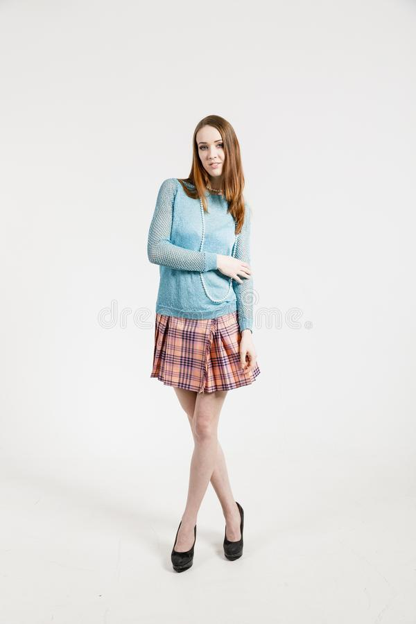 Изображение молодой женщины нося короткую юбку и пуловер бирюзы стоковое фото