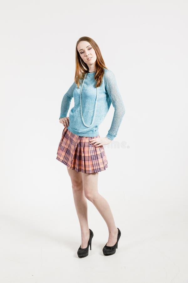 Изображение молодой женщины нося короткую юбку и пуловер бирюзы стоковые изображения rf