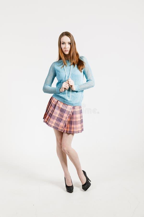 Изображение молодой женщины нося короткую юбку и пуловер бирюзы стоковая фотография