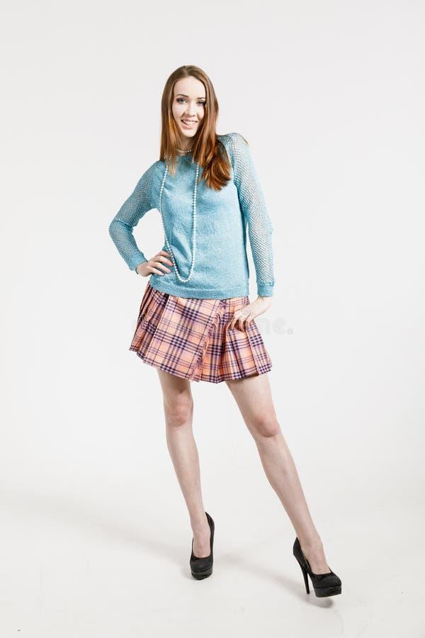 Изображение молодой женщины нося короткую юбку и пуловер бирюзы стоковое изображение