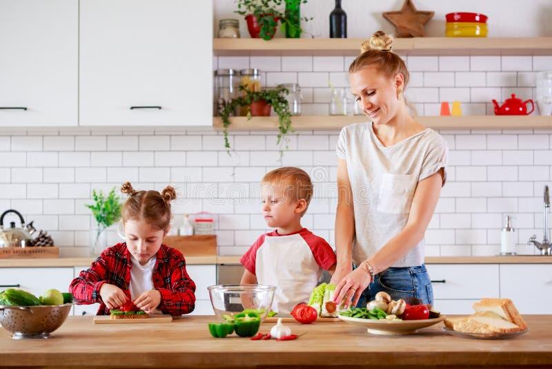 Изображение молодой матери с овощами вырезывания дочери и сына на таблице стоковая фотография rf