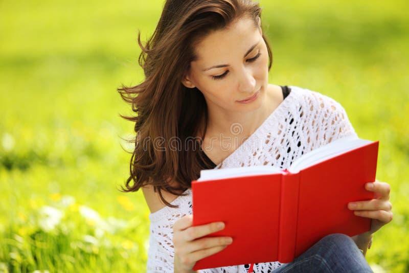 Изображение молодой красивой женщины в парке лета читая книгу стоковые фотографии rf