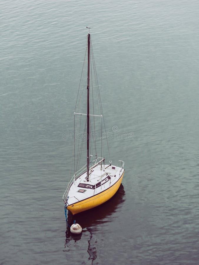 Изображение небольшого желтого парусника ставя на якорь рядом с томбуем в спокойной воде стоковая фотография