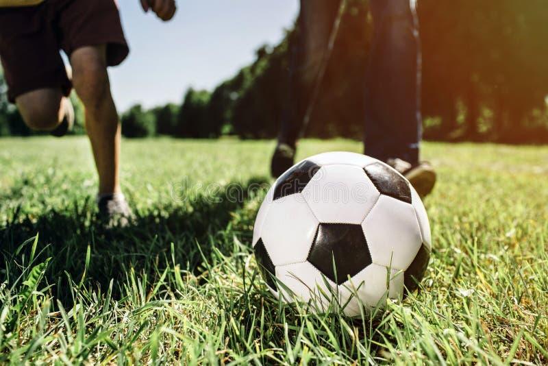 Изображение ног 2 людей играя футбольную игру Они играют на зеленой и сочной траве Солнечное снаружи стоковые фото