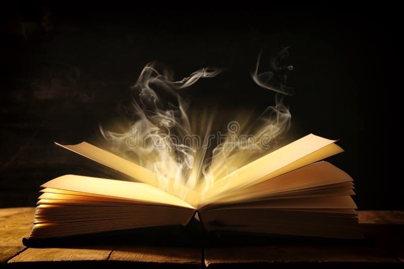 изображение открытой античной книги над деревянным столом стоковые фото