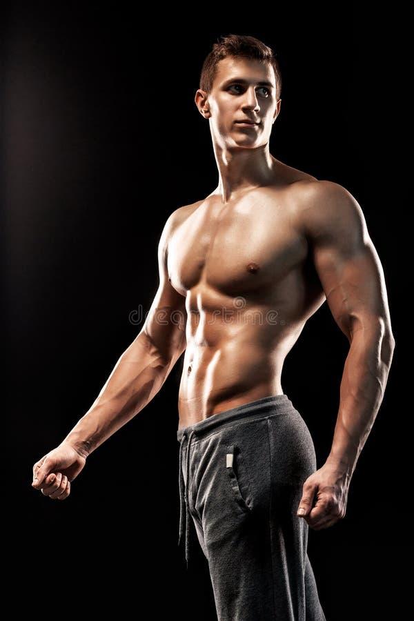 Изображение очень мышечного человека представляя с нагим торсом стоковое фото