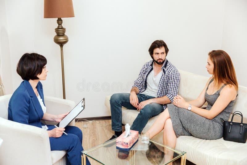 Изображение пар сидя совместно на софе и смотря друг к другу очень серьезно Доктор смотрит их и стоковое изображение