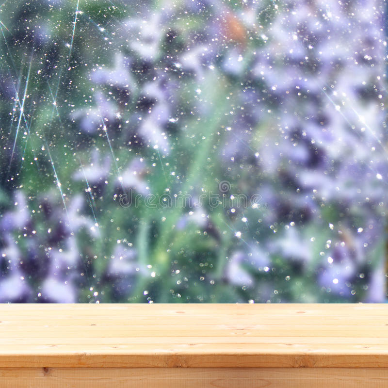 Изображение передних деревенских деревянных доск и предпосылка красивого поля цветков bokeh освещает верхний слой подготавливайте стоковое изображение