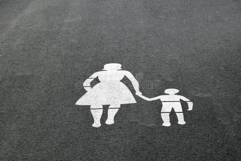 Изображение пешеходов женщины и мальчика нарисовано с белой краской на сером асфальте стоковое фото rf