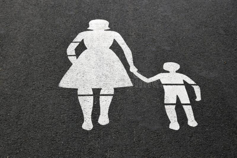 Изображение пешеходов женщины и мальчика нарисовано с белой краской на сером асфальте стоковые изображения