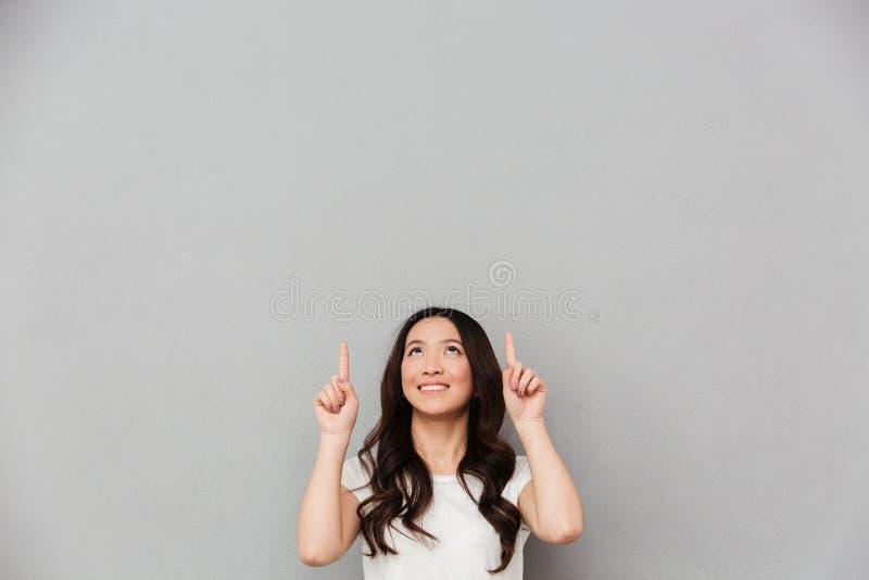 Изображение прелестной приветливой женщины в вскользь футболке указывая finge стоковое изображение