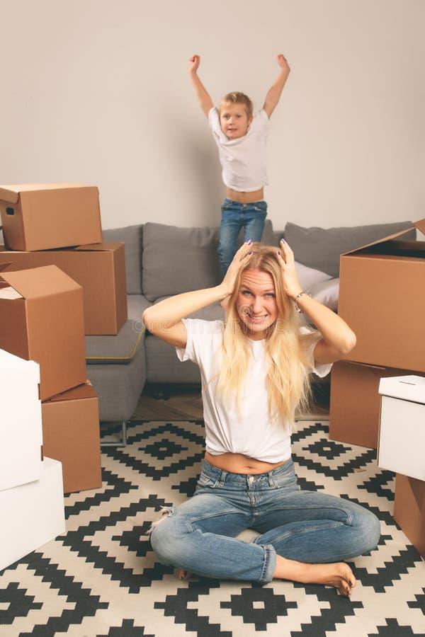 Изображение раздражанной матери сидя на поле среди картонных коробок и сына скача на кресло стоковая фотография rf