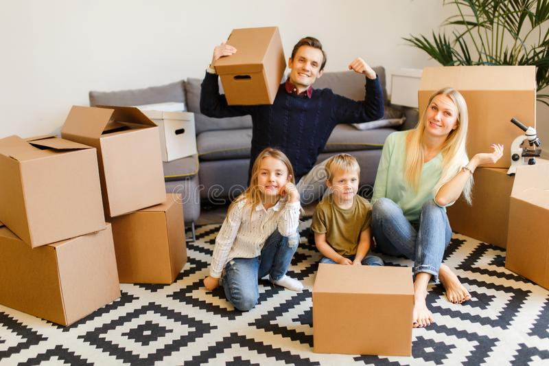 Изображение родителей с детьми сидя на поле среди картонных коробок стоковое изображение rf