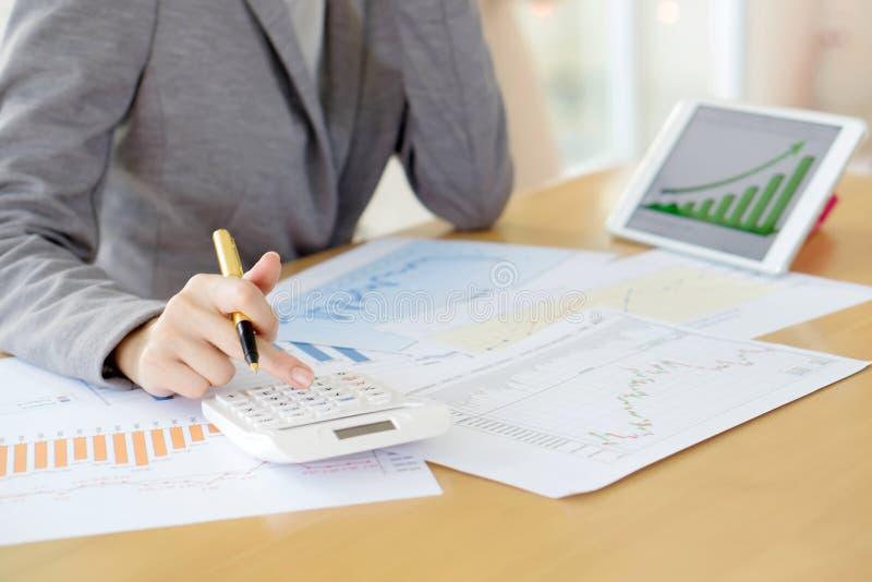 Изображение руки женщины с калькулятором и бумагами стоковое изображение