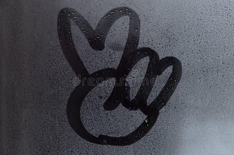 Изображение символа мира нарисовано с пальцем на поверхности misted стеклянного окна Пальцы сочетания из 2 стоковая фотография rf