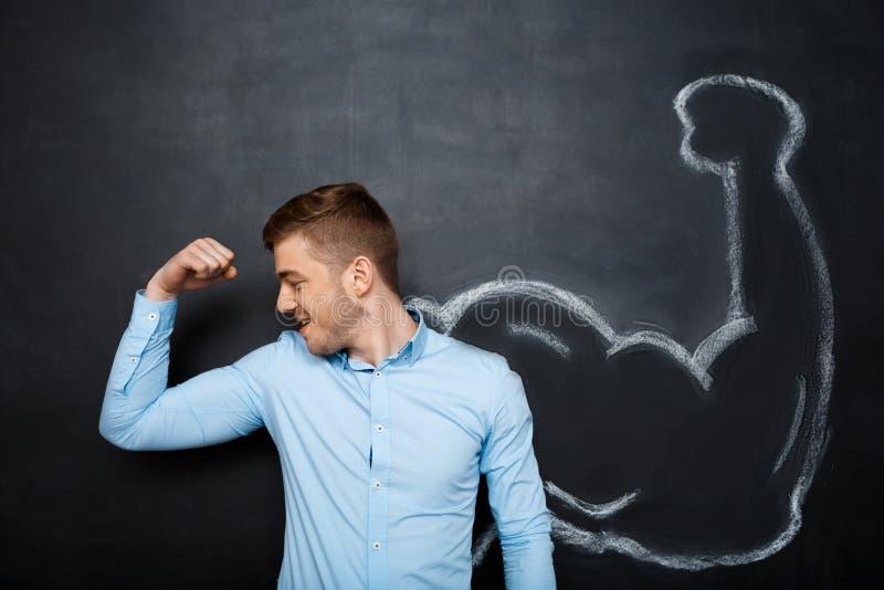 Изображение смешного человека с поддельной мышцей подготовляет стоковые фото