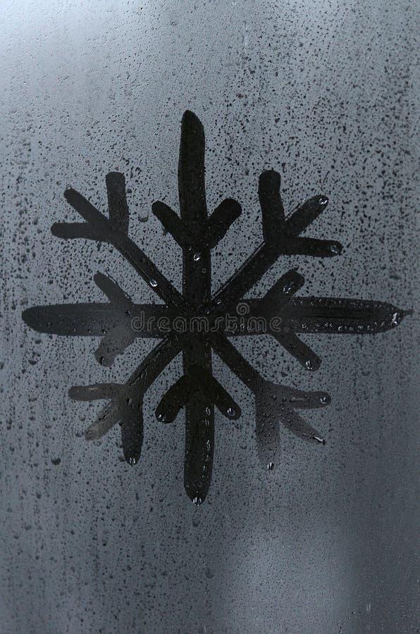 Изображение снежинки нарисовано с пальцем на поверхности misted стеклянного окна Морозная погода стоковые изображения