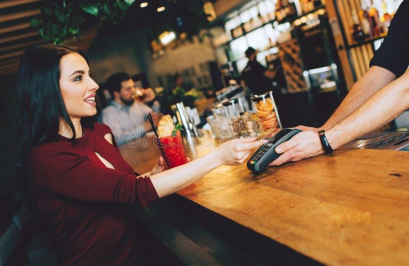 Изображение сногсшибательной девушки сидя близко к бармену и оплачивая для ее заказа Она дает кредитную карточку к бармену к опла стоковое изображение rf