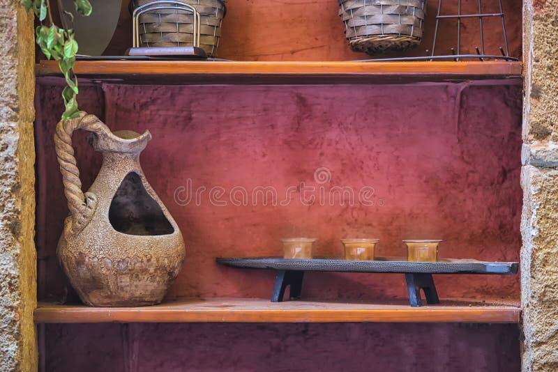 Изображение старой handmade винтажной вазы с фонариками на деревянной полке с красной бетонной стеной на предпосылке стоковое изображение rf