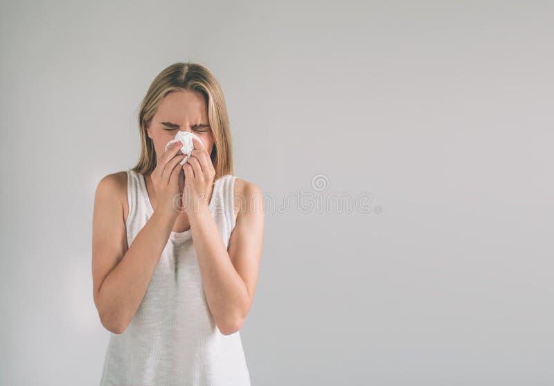 Изображение студии от молодой женщины с носовым платком Больная изолированная девушка имеет жидкий нос Женская модель делает лече стоковые изображения rf