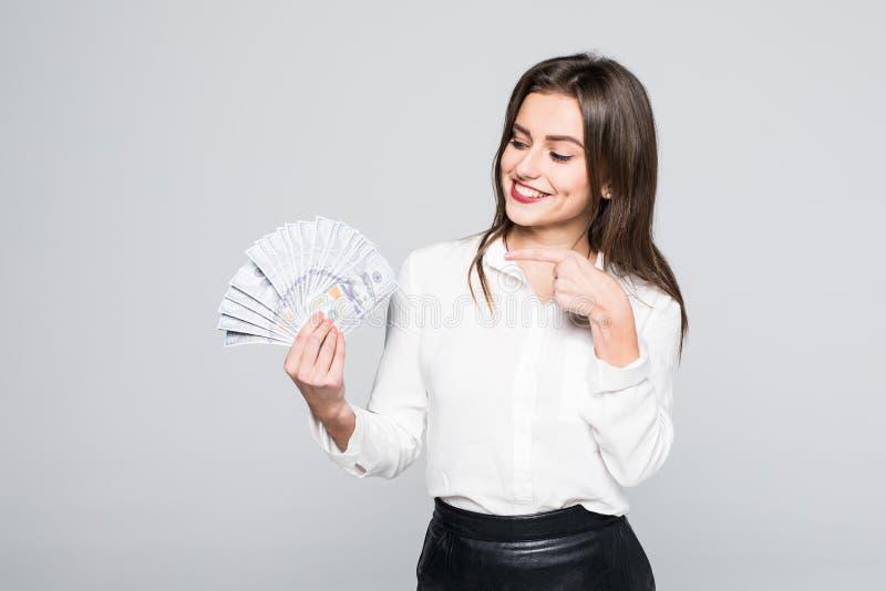 Изображение счастливого положения молодой женщины изолированного над белой предпосылкой держа указывать денег стоковая фотография rf