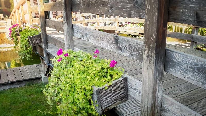 Изображение тонизированное крупным планом красивый расти цветков в баках на старом деревянном мосте над каналом воды в европейско стоковая фотография rf