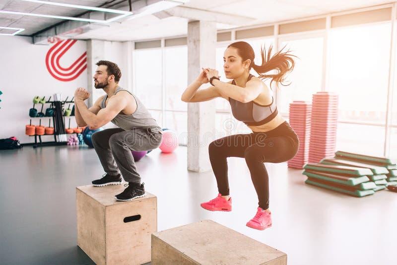 Изображение тонкого и крепкого молодого человека и женщины делая скачки на платформе Трудная тренировка но они делают стоковые фотографии rf