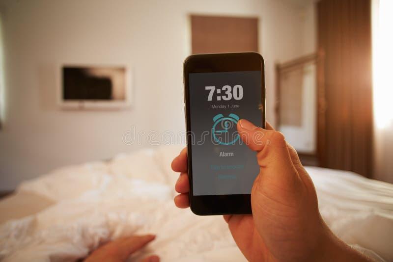 Изображение точки зрения персоны в кровати поворачивая сигнал тревоги телефона стоковое изображение rf