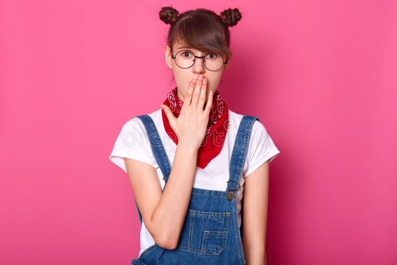 Изображение удивленного темного с волосами подростка со смешными banches, покрывает рот с рукой, носит футболку, прозодежды, стек стоковые изображения rf